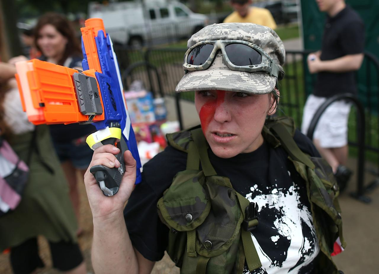 WASHINGTON, DC - JULY 03: Lauren Wagner holds a toy gun during a rally on the grounds of the Washington Monument July 3, 2013 in Washington, DC. Gun rights advocates participates in the Armed Toy Gun March on D.C. to raise money and toys for the Toys for Tots program. (Photo by Mark Wilson/Getty Images)