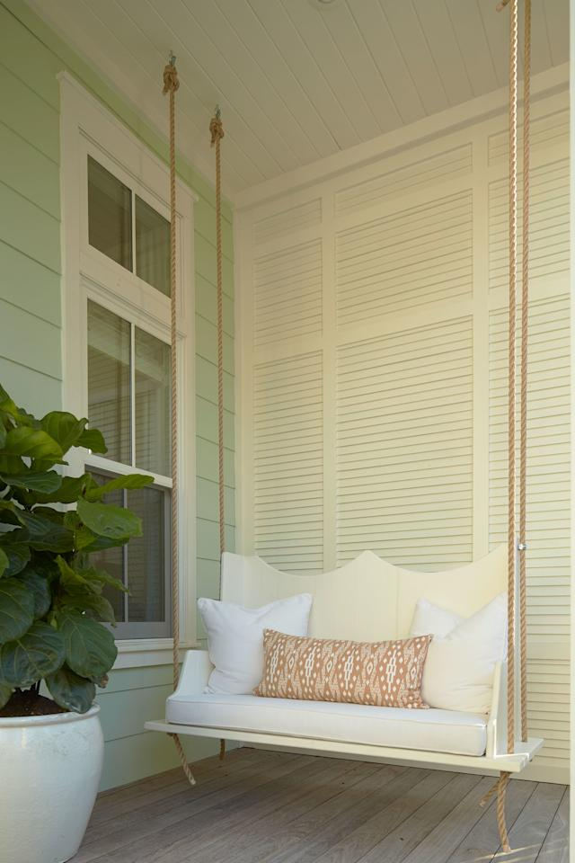 <p>A white wooden swing, built by a local craftsman, adds charm and seating on the porch.</p>