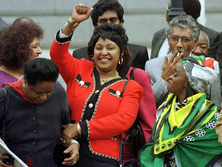 <p>Winnie Mandela dances outside Parliament after the approval of South Africa's new constitution on May 8, 1996. Despite fears that parties would not reach the required two-thirds consensus, the draft was passed with only 10 votes against it. Others are unidentified. (Photo: Mike Hutchings/pool/AP) </p>