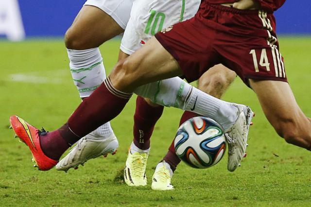 Russia's Vasili Berezutskiy (14) fights for the ball with Algeria's Sofiane Feghouli (10) during their 2014 World Cup Group H soccer match at the Baixada arena in Curitiba June 26, 2014. REUTERS/Damir Sagolj (BRAZIL - Tags: SOCCER SPORT WORLD CUP TPX IMAGES OF THE DAY)