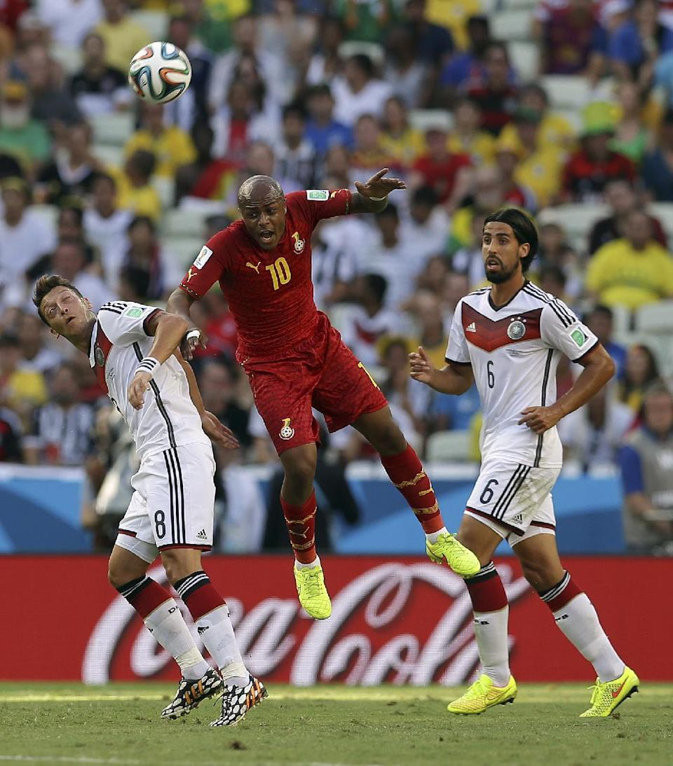 Ghana's Andre Ayew heads the ball between Germany's Mesut Ozil, left, and Sami Khedira, right, during the group G World Cup soccer match between Germany and Ghana at the Arena Castelao in Fortaleza, Brazil, Saturday, June 21, 2014. (AP Photo/Martin Mejia)