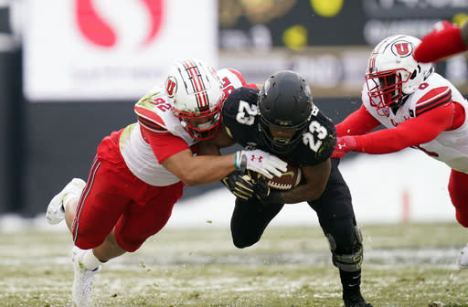Colorado running back Jarek Broussard, center, is stopped after a short gain by Utah defensive end Maxs Tupai, left, and linebacker Devin Lloyd in the first half of an NCAA college football game Saturday, Dec. 12, 2020, in Boulder, Colo. (AP Photo/David Zalubowski)
