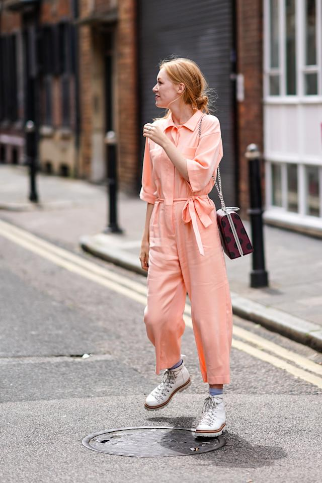 <p>For a feminine jumpsuit outfit that spans the seasons, go for a soft color like pink and mix in a playful bag and heft boots.</p>