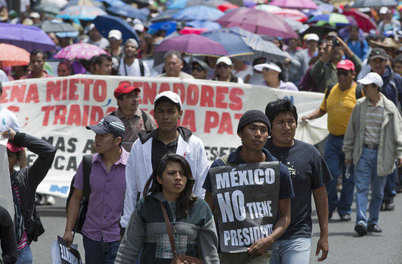 """Public school teachers march along Paseo de la Reforma, a main artery in the capital, to Los Pinos presidential residence in Mexico City, Wednesday, Aug. 28, 2013. The sign reads in Spanish """"Mexico has no president."""" Educators protesting a government reform program have in the span of a week disrupted international air travel, forced the cancellation of two major soccer matches, rerouted the planned route of the marathon and snarled already traffic-choked freeways. (AP Photo/Eduardo Verdugo)"""
