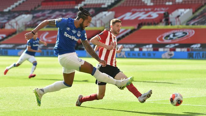 Striker Everton, Theo Walcott, berebut bola dengan bek Sheffield United, Chris Basham, pada laga lanjutan Premier League di Bramall Lane Stadium, Selasa (21/7/2020) dini hari WIB. Everton menang 1-0 atas Sheffield United. (AFP/Peter Powell/pool)