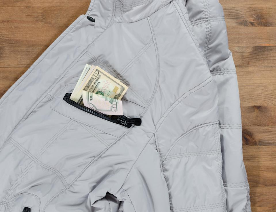 gentleman concept. jacket and dollars in the pocket on old wooden table