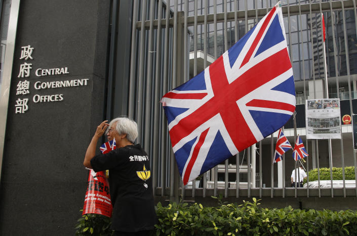 In this Thursday July 4, 2019, photo, Alexandra Wong, 63, a protester who's often seen raising the Union Jack at demonstrations and carried one into the legislative building on Monday night walks past one outside the Central Government Office in Hong Kong. Two decades after Britain handed the city over to China, its colonial-era flag is still a potent symbol of the democratic values that many Hong Kong residents hold dear.(AP Photo/Andy Wong)