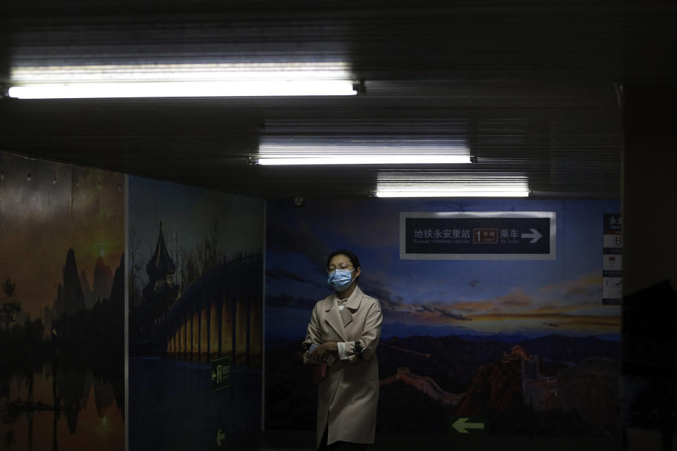 A woman wearing a face mask to help curb the spread of the coronavirus walks by pictures of China's tourism destination on display inside an underpass tunnel in Beijing, Monday, Oct. 19, 2020. (AP Photo/Andy Wong)
