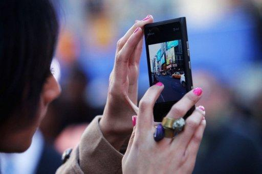 A woman takes a picture of Times Square on her cell phone. The Big Apple may not have California's weather, but tech fans at New York Internet Week say that in every other way the city is on course to become Silicon Valley 2.0