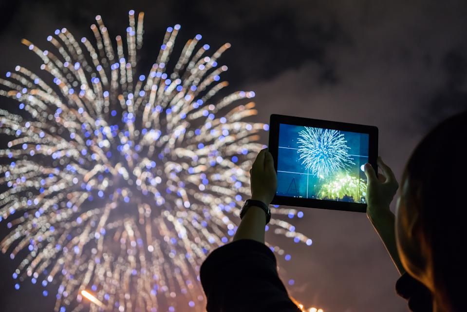 Using a digital tablet to capture images when watching a firework display.