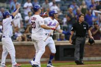 New York Mets' Jose Peraza, left, on-deck batter Pete Alonso (20) and Jeff McNeil, third from left, react at home plate after Peraza and McNeil scored on Dominic Smith's fifth-inning three-run double in the first baseball game of a doubleheader, Monday, June 21, 2021, in New York. Home plate umpire Ben May, right, looks on. (AP Photo/Kathy Willens)