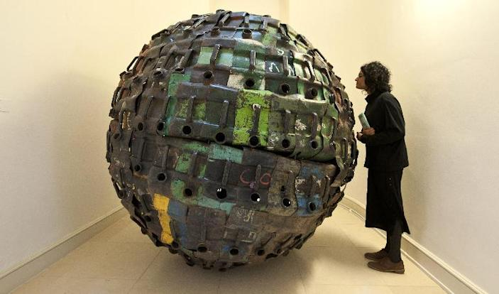 """A visitor looks at an artwork by Beninese artist Romuald Hazoumtitled """"Giant Ball """" displayed at the Contemporary African Art Fair at Somerset House in Central London on October 15, 2013 (AFP Photo/Will Oliver)"""