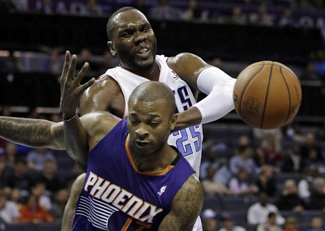 Charlotte Bobcats' Al Jefferson, back, is fouled by Phoenix Suns' P.J. Tucker, front, during the first half of an NBA basketball game in Charlotte, N.C., Friday, Nov. 22, 2013. (AP Photo/Chuck Burton)