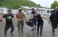 Migrants carry cricket gear after it arrived in Blazuj migrant camp in Bosnia's capital of Sarajevo Wednesday, May 19, 2021. The Rome-based Baobab Experience group brought cricket equipment for the migrants in the Blazuj camp and also the central town of Tuzla, offering a rare opportunity for relaxation and fun for the people who spend months, if not years, stuck in camps while fleeing war and poverty in their nations and chasing their dreams of a better future. (AP Photo/Kemal Softic)