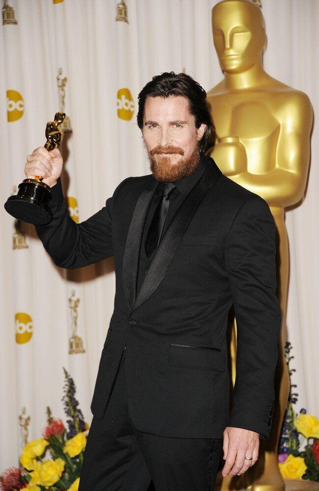 "Christian Bale holds his Oscar statue after winning for his role in ""The Fighter."""