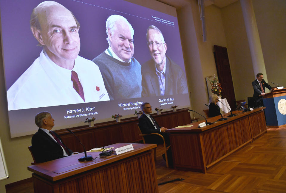 Thomas Perlmann, far right, Secretary of the Nobel Assembly announces the 2020 Nobel laureates in Physiology or Medicine during a news conference at the Karolinska Institute in Stockholm, Sweden, Monday Oct. 5, 2020. The prize has been awarded jointly to Harvey J. Alter, left on screen, Michael Houghton, center, and Charles M. Rice for the discovery of the Hepatitis C virus. (Claudio Bresciani/TT via AP)