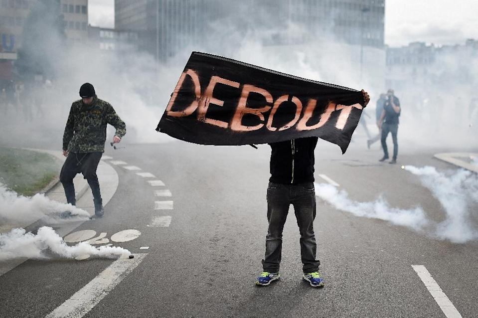 """A protester holds a sign reading """"Get up"""" during a demonstration against the government's planned labour law reforms on May 19, 2016 in Nantes (AFP Photo/Jean-Sebastien Evrard)"""