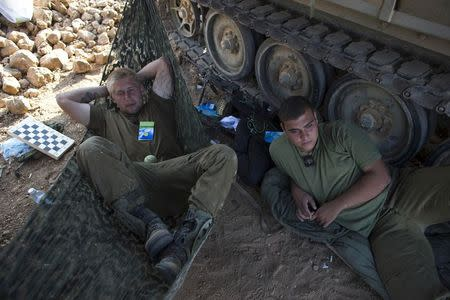 Israeli soldiers rest next to an armoured personnel carrier (APC) at a staging area outside the northern Gaza Strip July 27, 2014. REUTERS/Ronen Zvulun
