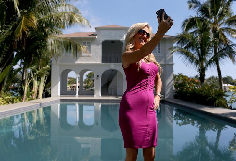 A television reporter takes a selfie in front of the pool and cabana during a tour of the former home of Al Capone on March 18, 2015 in Miami Beach, Florida: Joe Raedle/Getty Images