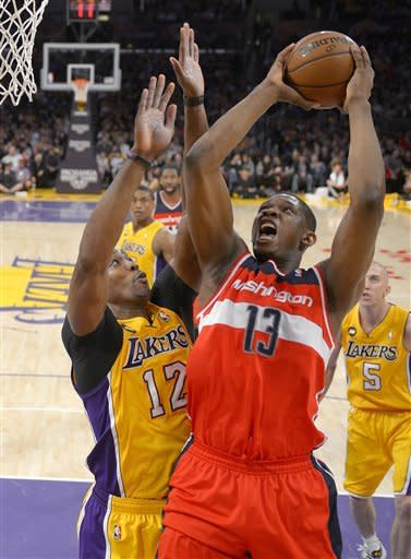 Washington Wizards forward Kevin Seraphin, right, of France, puts up a shot as Los Angeles Lakers center Dwight Howard defends during the first half of an NBA basketball game, Friday, March 22, 2013, in Los Angeles. (AP Photo/Mark J. Terrill)