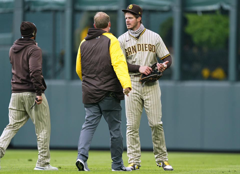 San Diego Padres manager Jayce Tingler, left, and a trainer check on right fielder Wil Myers after he ran into the wall catching a fly ball hit by Colorado Rockies' Garrett Hampson during the first inning of a baseball game Tuesday, May 11, 2021, in Denver. (AP Photo/David Zalubowski)