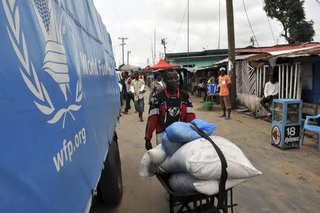 A resident of West Point neighbourhood, which has been quarantined following an outbreak of Ebola, pushes a wheelbarrow full of food rations from the United Nations World Food Programme (WFP) in Monrovia August 28, 2014. REUTERS/2Tango
