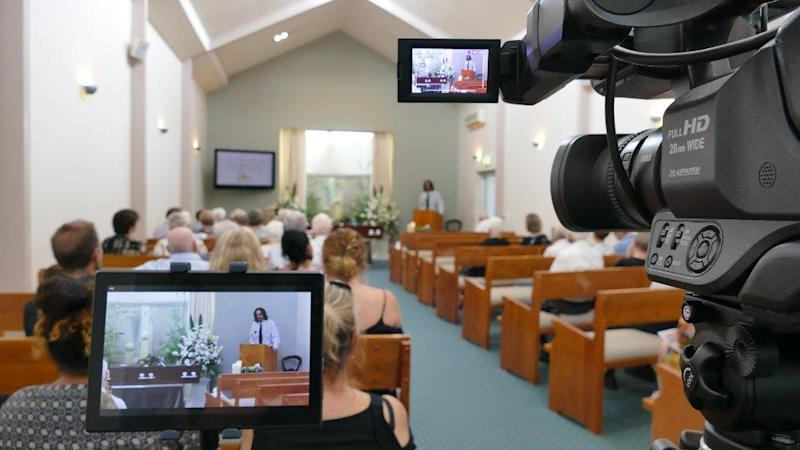 A Queensland funeral service being filmed as a man addresses the gathering.