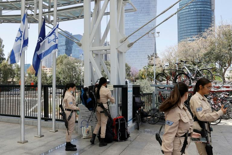 Israeli soldiers walk past flags lowered to half mast in the coastal city of Tel Aviv