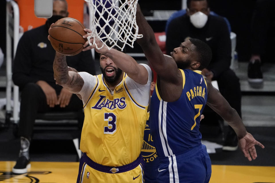 Los Angeles Lakers' Anthony Davis, left, grabs a rebound against Golden State Warriors' Eric Paschall during the first half of an NBA basketball game, Monday, Jan. 18, 2021, in Los Angeles. (AP Photo/Jae C. Hong)