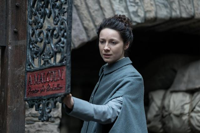 Claire examines the sign for A. Malcolm's print shop (Photo: Starz)