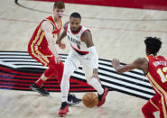 Portland Trail Blazers guard Damian Lillard, center, dribbles past Atlanta Hawks guard Kevin Huerter, left, during the first half of an NBA basketball game in Portland, Ore., Saturday, Jan. 16, 2021. (AP Photo/Craig Mitchelldyer)