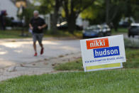 A person jogs past a school board yard sign Thursday, Oct. 7, 2021, in Worthington, Ohio. Across Ohio and the nation, parental protests over social issues like mask mandates, gender-neutral bathrooms, teachings on racial history, sexuality and mental and emotional health are being leveraged into school board takeover campaigns. (AP Photo/Jay LaPrete)