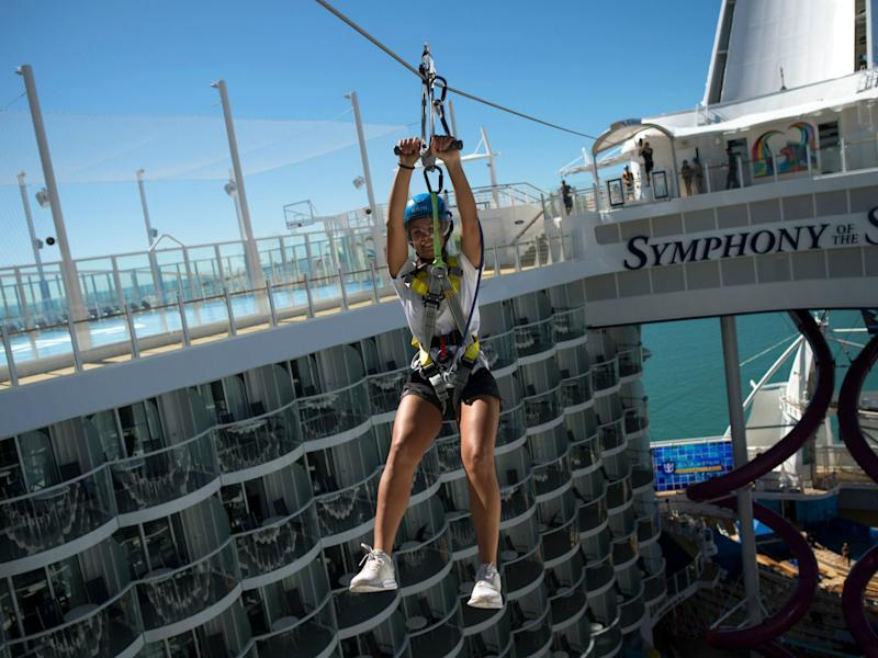 A woman slides down a zip-line aboard a Royal Caribbean's cruise ship. A man died after colliding with his wife on a zip line in Honduras while on their honeymoon: JORGE GUERRERO/AFP/Getty Images