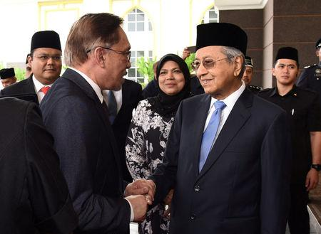 Politician Anwar Ibrahim shakes hands with Malaysian Prime Minister Mahathir Mohamad at National Palace in Kuala Lumpur, Malaysia May 16, 2018. Department of Information/Krish Balakrishnan/Handout via REUTERS