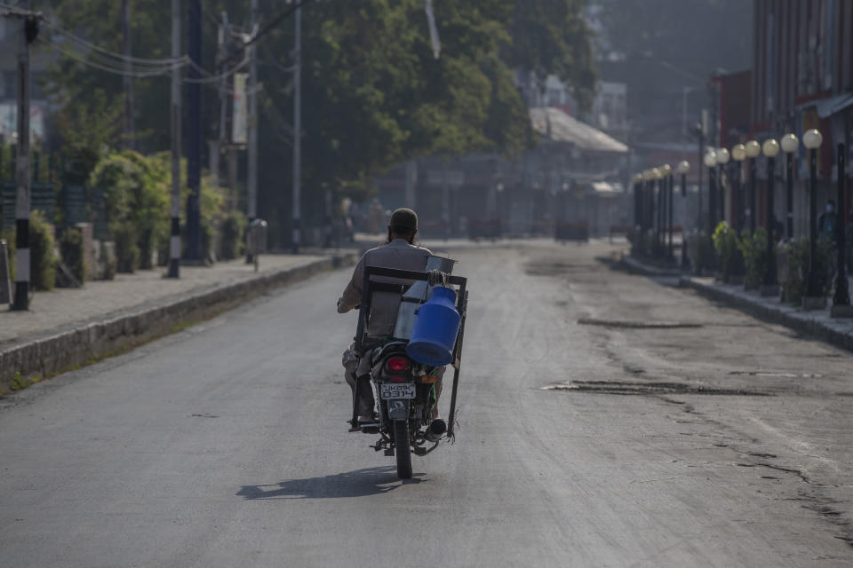 A Kashmiri milkman drives his motorcycle on a deserted street on the first anniversary of India's decision to revoke the disputed region's semi-autonomy, in Srinagar, Indian controlled Kashmir, Wednesday, Aug. 5, 2020. Last year on Aug. 5, India's Hindu-nationalist-led government of Prime Minister Narendra Modi stripped Jammu-Kashmir of its statehood and divided it into two federally governed territories. Late Tuesday, authorities lifted a curfew in Srinagar but said restrictions on public movement, transport and commercial activities would continue because of the coronavirus pandemic. (AP Photo/ Dar Yasin)