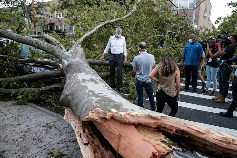 New York City Mayor Bill de Blasio talks with residents about damage from Tropical Storm Isaias, Tuesday, Aug. 4, 2020, in the Queens borough of New York. (AP Photo/Frank Franklin II)