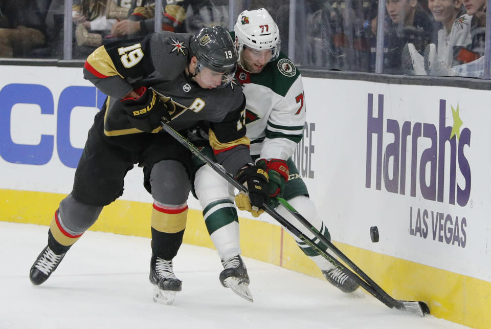 Vegas Golden Knights right wing Reilly Smith (19) and Minnesota Wild defenseman Brad Hunt (77) vie for the puck during the second period of an NHL hockey game Tuesday, Dec. 17, 2019, in Las Vegas. (AP Photo/John Locher)