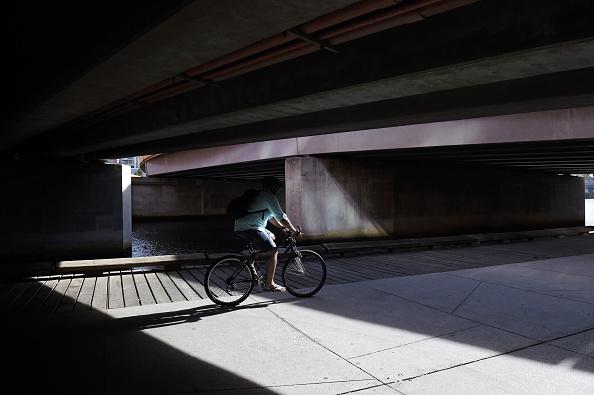 A cyclist rides under a bridge along the South Wharf Promenade beside the Yarra River in Melbourne.
