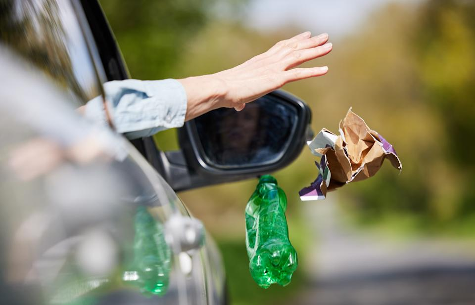 Man dropping rubbish out of car window. Source:Getty Images
