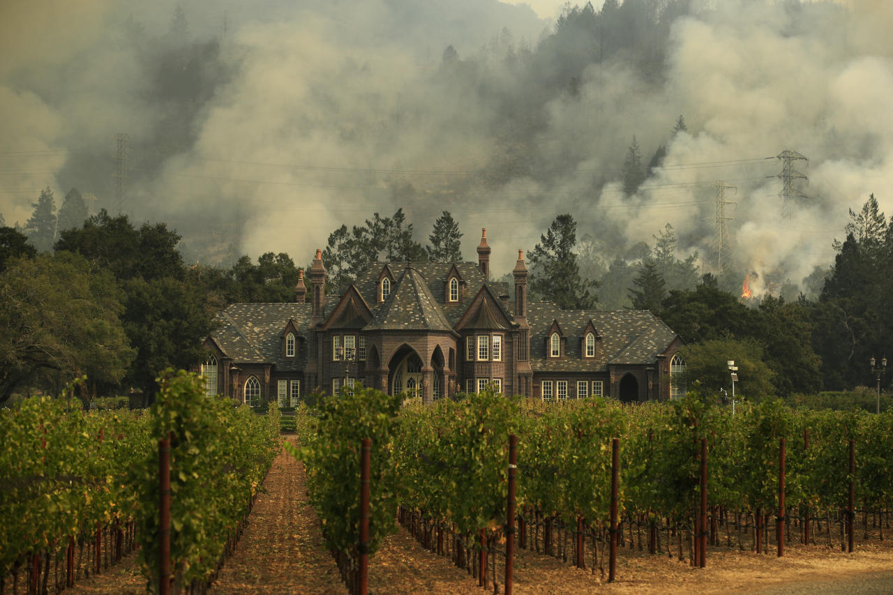 <p>A wildfire burns behind a winery Saturday, Oct. 14, 2017, in Santa Rosa, Calif. Fire crews made progress this week in their efforts to contain the massive wildfires in California wine country, but officials say strong winds are putting their work to the test. (Photo: Jae C. Hong/AP) </p>