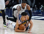 Denver Nuggets forward Michael Porter Jr., bottom, cover the ball as San Antonio Spurs guard Dejounte Murray defends in the first half of an NBA basketball game Friday, April 9, 2021, in Denver. (AP Photo/David Zalubowski)