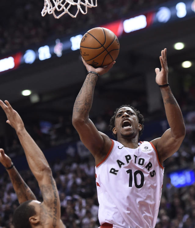 FILE - In this May 1, 2018, file photo, Toronto Raptors guard DeMar DeRozan (10) scores over Cleveland Cavaliers guard George Hill during the first half of Game 1 of an NBA basketball playoffs Eastern Conference semifinal, in Toronto. Two people familiar with the situation say San Antonio and Toronto have reached an agreement in principle on a trade that will send Kawhi Leonard to the Raptors and DeMar DeRozan to the Spurs. One of the people says the Spurs also are sending Danny Green to the Raptors as part of the deal. Both people spoke to The Associated Press on condition of anonymity Wednesday, July 18, 2018, because the deal has not been finalized. (Nathan Denette/The Canadian Press via AP, File)