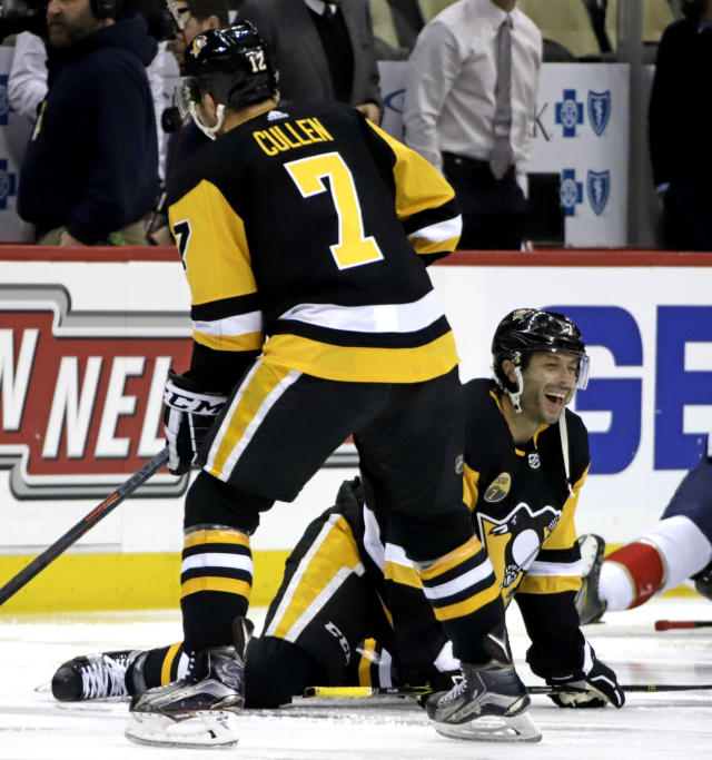 Pittsburgh Penguins' Matt Cullen, lower right, stretches during warmups for his 1,500th career NHL hockey game before facing the Florida Panthers in Pittsburgh, Tuesday, March 5, 2019. The entire Penguins team wore Cullen's No. 7 jerseys during warmups. Cullen is the second American-born player to reach the 1,500 game plateau. Chris Chelios is first with 1,651 NHL games played. (AP Photo/Gene J. Puskar)