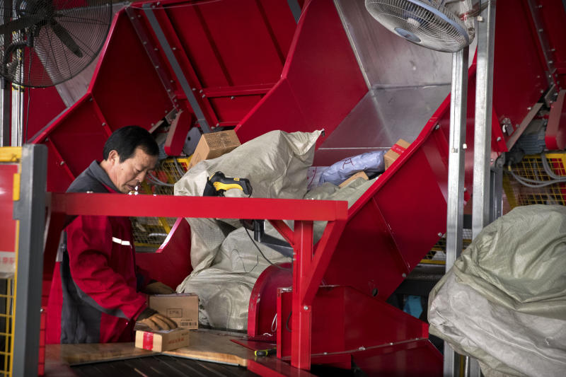 A worker places packages onto a conveyor belt in an automated parcel sorting facility for e-commerce retailer JD.com in Tongzhou, suburban Beijing, Sunday, Nov. 11, 2018. Online shoppers spent more than $14 billion within the first two hours of China's annual buying frenzy on Sunday, once again breaking records as the consumer tradition enters its 10th year. (AP Photo/Mark Schiefelbein)