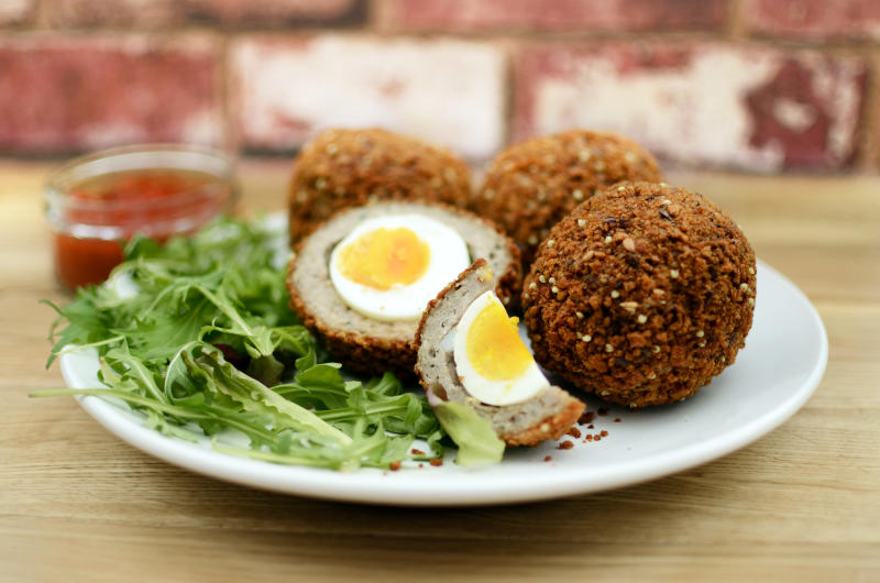 """Free range eggs covered in pork meat with a breadcrumb coating, served with salad and a tomato dip."""