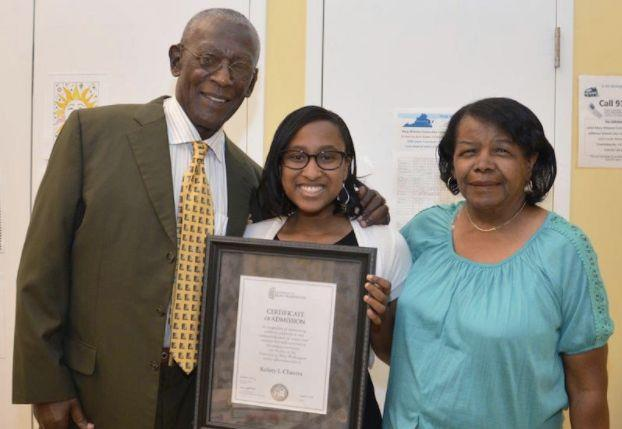 A student receives a scholarship from Dr. Rick Turner and current Albemarle-Charlottesville NAACPPresident Janette Martin on Aug. 8, 2016.