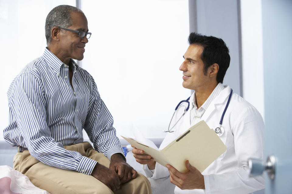 Doctor In Surgery With Male Patient Reading Notes Smiling To Each Other.