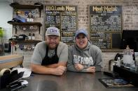 Byron Stephenson and his wife Stacie, owners of the The Shed Market, a barbecue restaurant, pose for a photo at their storefront counter on Wednesday, Dec. 16, 2020, in Abilene, Texas. (AP Photo/Tony Gutierrez)