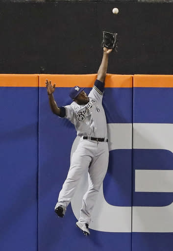 FILE - In this Friday, April 26, 2019 file photo, Milwaukee Brewers center fielder Lorenzo Cain (6) catches a ball hit by New York Mets' Todd Frazier for an out during the second inning of a baseball game in New York. Everyone has seen an outfielder receive a tip of the cap or a jubilant fist bump from a pitcher after a home run robbery. This is a story about what happens after they leave the field. (AP Photo/Frank Franklin II, File)