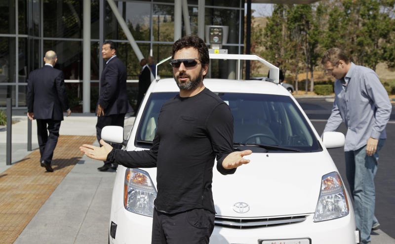 Google co-founder Sergey Brin gestures after riding in a driverless car with California Gov. Edmund G Brown Jr., left, and state Senator Alex Padilla, second from left, to a bill signing for driverless cars at Google headquarters in Mountain View, Calif., Tuesday, Sept. 25, 2012. The legislation will open the way for driverless cars in the state. Google, which has been developing autonomous car technology and lobbying for the legislation has a fleet of driverless cars that has logged more than 300,000 miles (482,780 kilometers) of self-driving on California roads. (AP Photo/Eric Risberg)